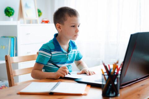 Junge bearbeitet Aufgaben beim Online-Unterricht